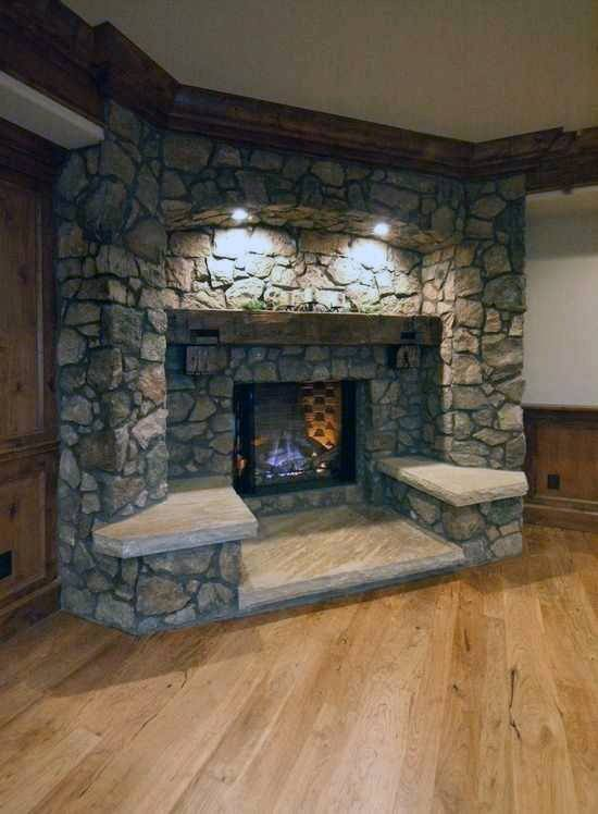 Rustic stone corner fireplace design with hardwood flooring